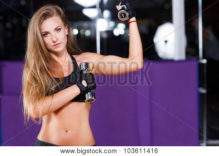 Athletic young woman with long hair wearing in black top and breeches posing with dumbbells and looking at camera on the sport equipment background in the gym waist up