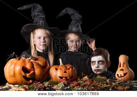 Halloween. Two little witches, skull surrounded by pumpkins and foliage