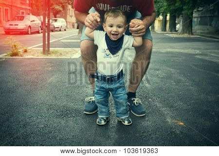 Cute Smiling Little Boy In Father Hands