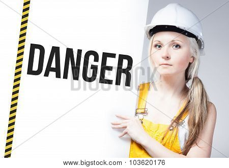 Worker Holding Danger Sign On Information Board