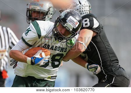 INNSBRUCK, AUSTRIA - JULY 12, 2014: DB Arno Andreas (#8 Raiders) tackles WR Johannes Prammer (#88 Dragons) during an Austrian football league game.