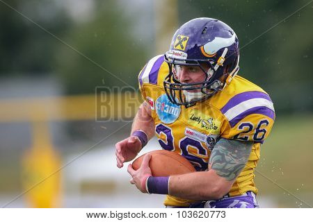 VIENNA, AUSTRIA - JULY 13, 2014: RB Craig Sedunov (#26 Vikings) runs with the ball during an Austrian football league game.