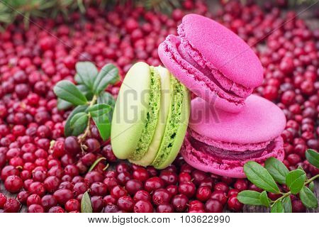 French Macarons with cranberries on wooden background