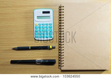Calculator,pen,pencil And Book On Wooden Table. Top View