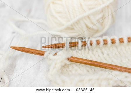 Sample Of Knitting From Woolen Yarn White Color On Wooden Knitting Needles