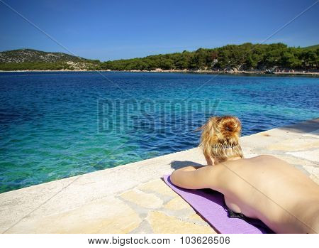 Young Redhead Woman Sunbathing On The Beach By Clear Sea, Croatia Dalmatia