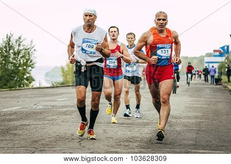 two elderly runners run ahead of a large group of runners