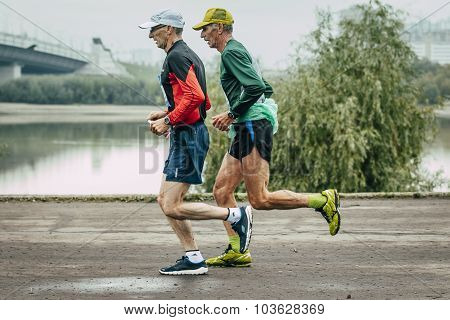 two elderly joggers run along embankment of river
