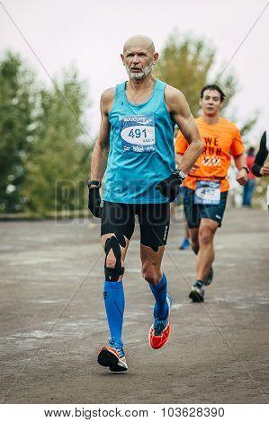 elderly athlete ahead of younger runner