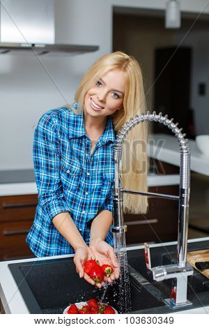Beautiful young woman with plate of strawberries in kitchen.