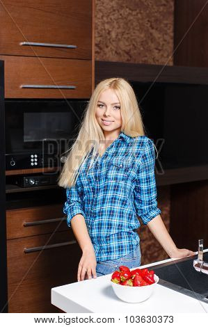 Beautiful young blonde woman preparing healthy food in the kitchen.