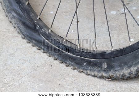 Old Bicycle Wheel With Flat Tyre On Road