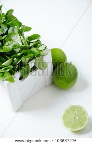 Watercress Salad In White Wooden Box With Limes Around
