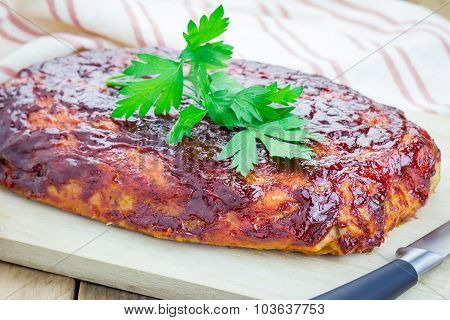 Homemade Meatloaf With Ketchup And Parsley On A Wooden Board