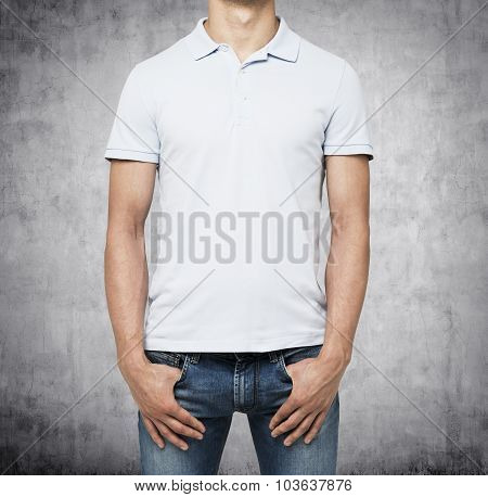 A Man In A White Polo Shirt And Denims Holds His Hands In Pockets. Concrete Background.