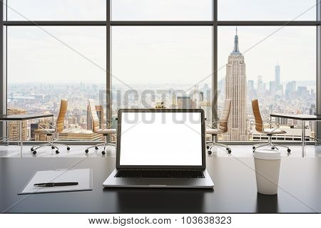 A Workplace In A Modern Panoramic Office In New York. A Laptop With White Screen, Notepad And A Coff