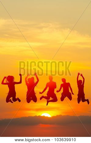 Teenage Boys And Girls Jumping High In The Air Against Colorful Sky During Summer Sunset