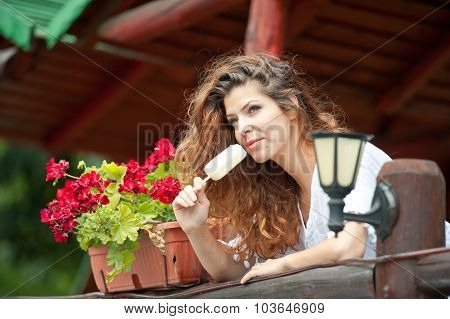 Beautiful female portrait with long brown hair eating ice cream near a pot with red flowers outdoor.