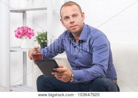 Handsome Businessman Sitting On Couch With Laptop At Home In The Living Room, Looking Camera