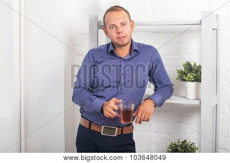 Man Businessman Standing In An Office Off The Shelves With A Mug Of Tea.