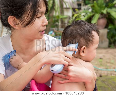 Mother Cutting Baby Hair By Hair Clipper