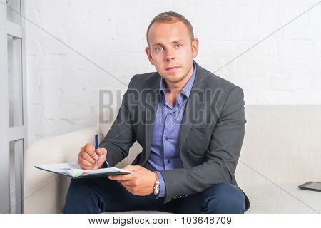 Handsome Businessman Sitting On Couch With Notebook At Home In The Living Room, Looking Camera