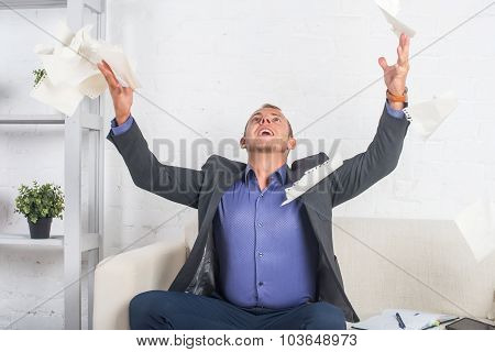 Excited Businessman Throwing Papers At The Office