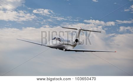 Private jet in the air with clouds in the background