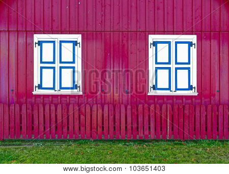 Red facade with colorful shutters. Residential house