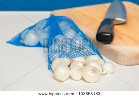 Fresh pearl onions on a white counter