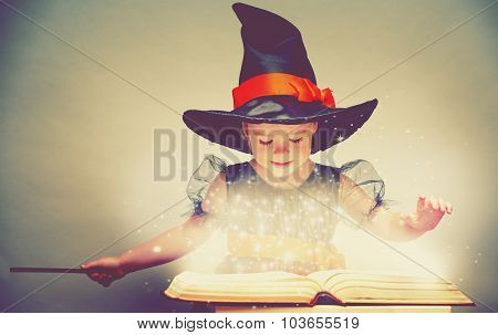 Halloween. Cheerful Little Witch With A Magic Wand And Glowing Book