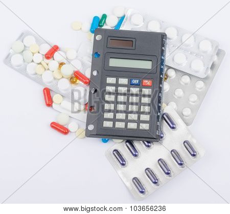 Tablets with capsules in blister packs and calculator lying on top