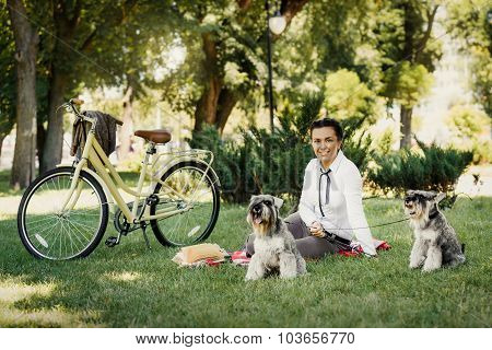Young Woman With Dogs And Bicycle Having Picnic In The Park