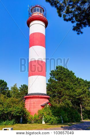 Striped lighthouse in the forest. Nida town