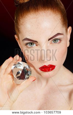 Portrait of a beautiful girl with precious stone isolated on a black background.