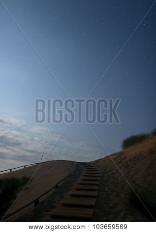 Sandy dunes with wooden stairs during nighttime. Lithuania.