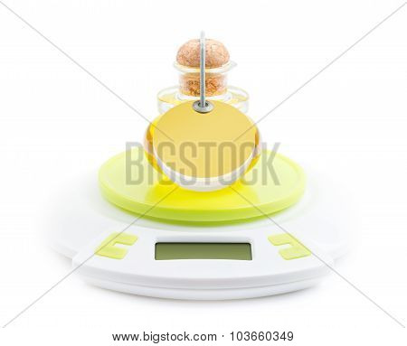 Bottle of olive oil stands on kitchen electronic scales