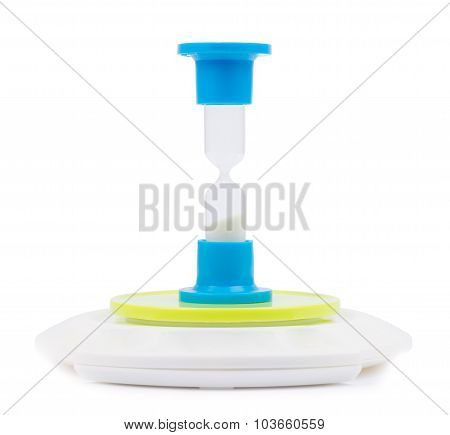 Hourglass standing on electronic scales.
