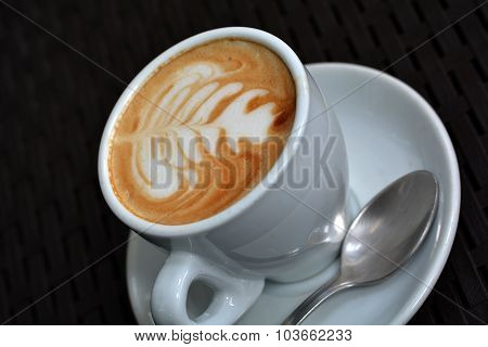 Cup of delicious foamy cappuccino on the black background