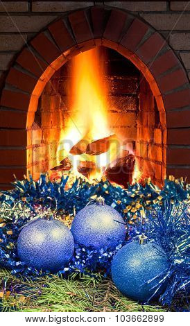 Blue Christmas Balls On Spruce Tree And Fireplace
