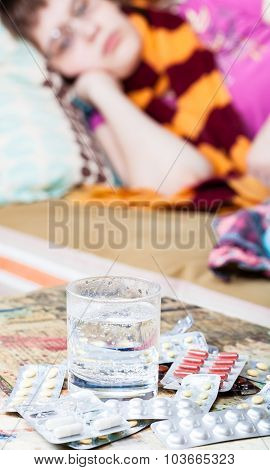 Glass With Water And Medicaments On Table