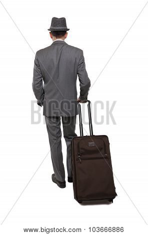 Rear view one caucasian business traveler man walking with suitcase