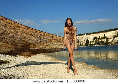 Beautiful Woman In Fashion Clothes Posing Beside Lake