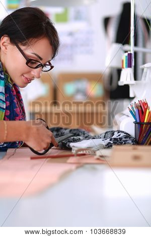 Fashion designer cutting textile next to a sewing machine