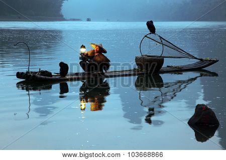 Chinese Man Fishing With Cormorants Birds In Yangshuo, Guangxi Region, Tradition