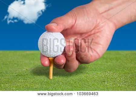 Golfer places a golf ball and tee in the ground