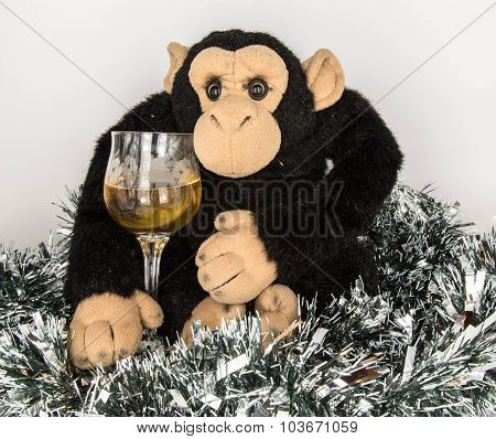 Black Toy Monkey With Brilliant New Year's Tinsel And A Glass Of Wine On A White Background