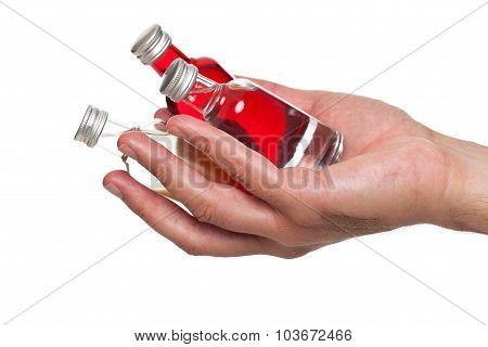 Hand holding little bottles of liquor