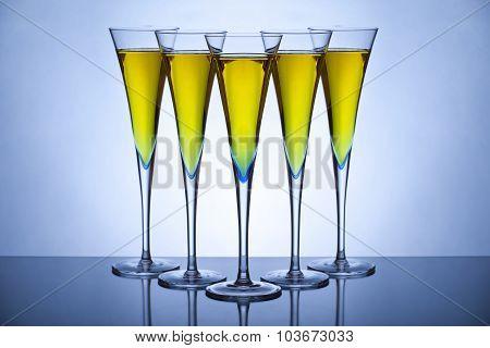 Five champagne glasses back lit