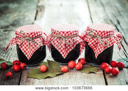 Three Jars Of Jam And Hawthorn Berries On Rustic Table